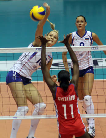nakhon pathom, thailand, august 5, 2011: lulila morozova (white jersey, no.10),russian female volleyball player spikes the ball through  blocking of cuba players leanny castaneda simon (red  jersey, no.11 )at first game for 2011 fivb world grand prix