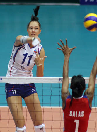nakhon pathom, thailand, august 5, 2011– ekaterina gamova (white jersey ),russian female volleyball player spikes the ball over blocking of cuba players leanny castaneda simon (red  jersey, no.11 )at the first game  for 2011 fivbworld grand prix