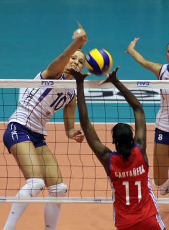 nakhon pathom, thailand, august 5, 2011: lulila morozova (white jersey, no.10),russian female volleyball player spikes the ball through  blocking of cuba players leanny castaneda simon (red  jersey, no.11 )at first game for 2011 fivb world grand prix  Stock Photo - 10165066