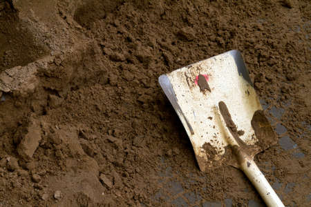 mattock: A working shovel and brown clay at under construction street
