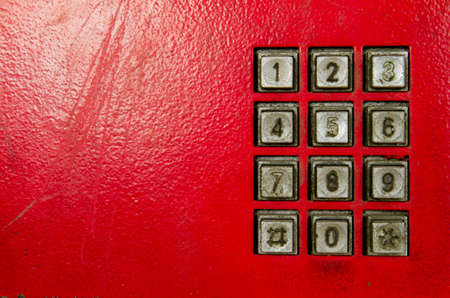 An old red public telephone panel