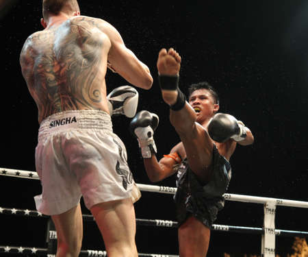 BANGKOK,THAILAND-DECEMBER 16:Buakaw Por. Pramuk (Thailand ,black shorts) in action with Vitaly Hurkou (Belarus ,white shorts) in the  Final round match of THAI FIGHT 2012,at King Chulalongkorn Monument Square, Bangkok, Thailand