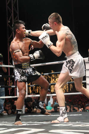 BANGKOK,THAILAND-DECEMBER 16:Buakaw Por. Pramuk (Thailand ,black shorts) in action with Vitaly Hurkou (Belarus,white shorts) in the  Final round match of THAI FIGHT 2012,at King Chulalongkorn Monument Square, Bangkok,Thailand