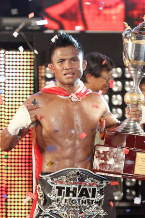 BANGKOK,THAILAND-DECEMBER 16:Buakaw Por. Pramuk from Thailand celebrates his winning and show  the trophy in the  Final round match of  THAI FIGHT 2012,at King Chulalongkorn Monument Square, Bangkok,Thailand
