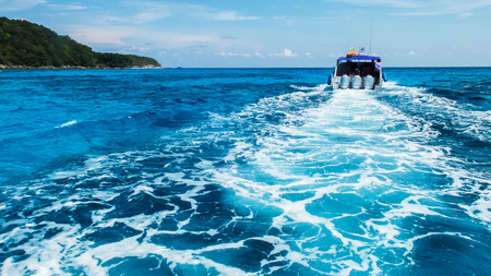 wake wash: Boat Wake Prop Wash in Clear Blue Ocean Sea from Behind of Soft Focus Speed Boat in Sunny Day Stock Photo