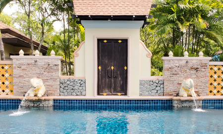 water feature: Luxury Outdoor Swimming Pool with Thai Style Decoration and Elephant Water Feature Editorial