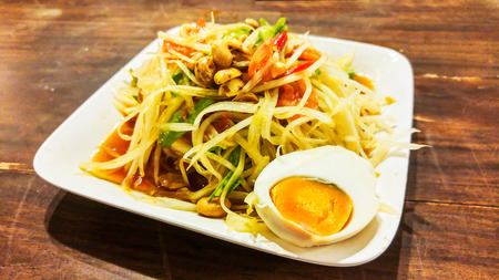 somtum: Famous Thai Traditional Food called Somtum or Papaya Salad on Wooden Table