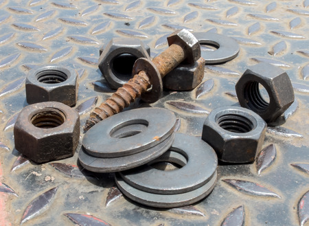 Grunge Screw Nuts Bolts and Rings for Repair on Diamond Steel Plate Stock Photo