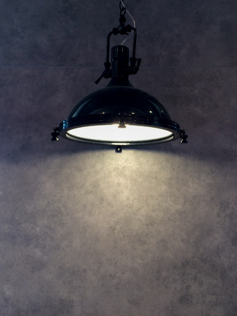 lamp shade: Lamp Shade from Modern Black Metal Lamp Hanging on Gray Wall Background with Copyspace to input Text used as Template Stock Photo