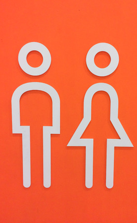 nude male: White Wooden Man and Woman Restroom Icon on Orange Wall Background Stock Photo