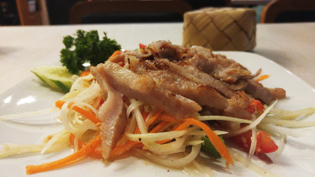 isaan: Som Tam or Papaya Salad with Grill Pork and Sticky Rice in Bamboo Container Stock Photo