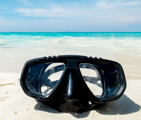 subsea: Vacation Start Here Concept, Scuba Diving Equipment On The White Sea Sand Beach with Crystal Clear Sea and Sky in Background used as Template