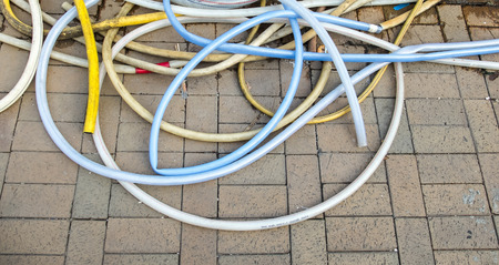 plastic conduit: Old Abandoned Multi Color Rubber Tube on Brick Stone Floor in Public Park
