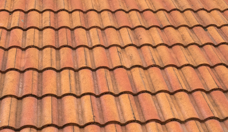 tile roof: Grunge Orange Corrugated Roof Tile Stock Photo