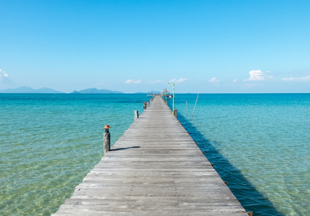 Vacation Time Concept, Wooden Path Between Crystal Clear Blue Sea and Sky from Beach of Island to The Pier in Thailand