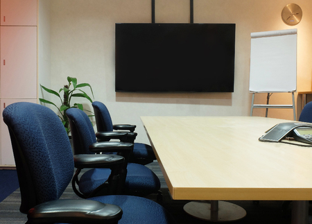 ergonomic: The Empty Meeting Room with Used Office Furniture. Conference Table, Fabric Ergonomic Chairs, Blank Screen and Blank Paper Flip Chart used as Template Stock Photo