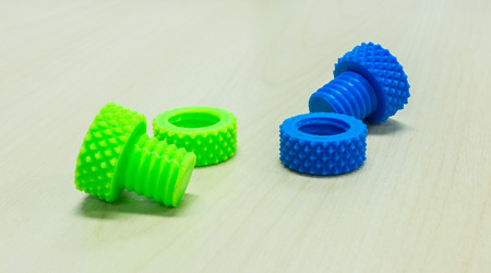 nuts and bolts: Colorful Creative Plastic Screw Nuts Bolts and Rings made by 3D Printer on Wooden Table Stock Photo
