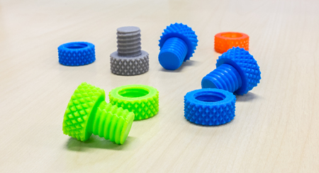 bolts and nuts: Colorful Creative Plastic Screw Nuts Bolts and Rings made by 3D Printer on Wooden Table Foto de archivo