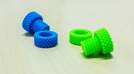 tuercas y tornillos: Colorido creativo de rosca de pl�stico Tuercas Tornillos y anillos realizados por la impresora 3D en la tabla de madera