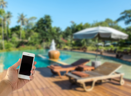 Close up of Male Hand Holding Smart Mobile Phone with Blank Screen on The Blur Swimming Pool with Various Tree in Luxury Hotel used as Template to input Text or Photo, Business Concept
