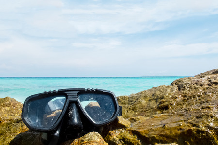 subsea: Vacation Start Here Concept, Scuba Diving Equipment On The Sea Rock of The Beach at The Corner with Crystal Clear Sea and Sky in Background as Copyspace used as Template to input Text