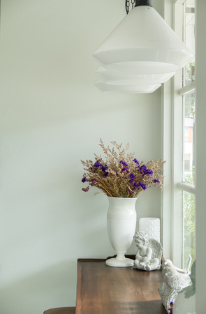 Beautiful Bouquet of Flowers in White Shiny Ceramic Flowerpot on Rustic Wooden Table at The Corner of Luxury White Living Room by The Window of Natural Garden View with White Hanging Lamps on Ceiling