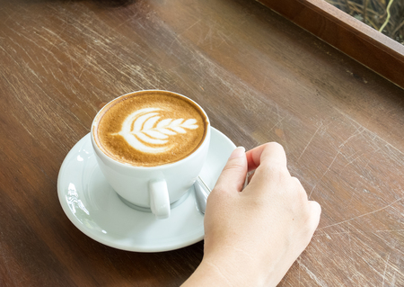 Start The Day with Good Cup of Coffee Concept. Perspective View of Asian Woman Hand Holding Cup of Cappuccino Coffee with Tree Design Foam on Wooden Panel Table by The Window of Nature Garden View
