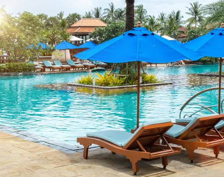 Relax by The Pool in Luxury Hotel on The Island of Thailand. Couple of Wooden Chair under The Umbrella by The View of Beautiful Luxury Swimming Pool with Various Type of Palm Trees in The Garden.