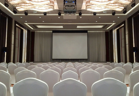 Conference Meeting Room with ceiling LED lights, Row of White Chairs, with Stage and Empty Screen for Business Meeting, Conference, Training Course, used as Template of The Elegant Design Office