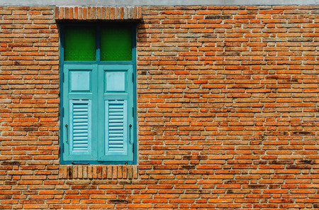 Big Blue Wooden Windows with Green Glasses at The Corner of Vintage Style Orange Brown Brick Wall of Ancient Building as Copyspace used as Template to mock up or input Text