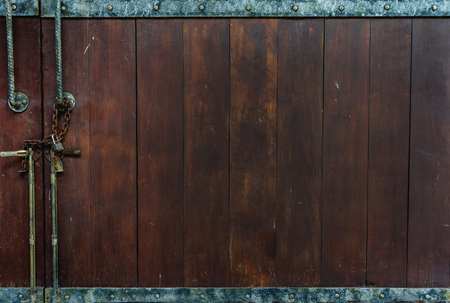 Closed Vintage Dark Brown Wooden Panel Door with Metal Line and Metal Button above and below with Rustic Metal Lock and Door Knob at The Corner as Copyspace used as Template to mock up or input Text Imagens