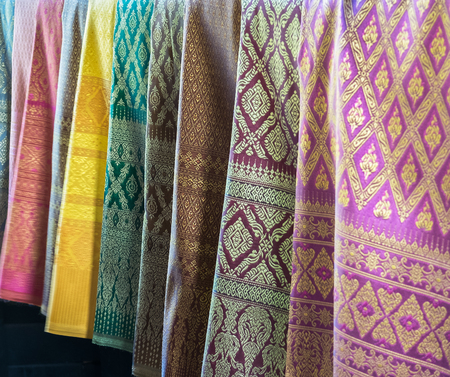 Beautiful Row of Traditional Colorful Thai Silk Fabric Textile with Seamless Pattern of Vintage Thai Design Style hanging in The Fashion Store for Sell used as Template
