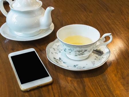 Antique Tea Set with White Jar and Beautiful Cup Full of Herbal Tea on Wooden Table for Tea Break Time or Breakfast and Blank Screen of Mobil Phone for Mock up Photo or input Text. Business Concept