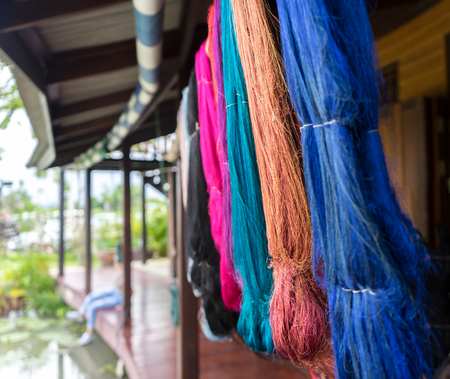 Various Colorful Dyeing Silks such as Blue, Brown, Pink Hanging from The Roof in Pattern after Thai Style Dyeing before Make some Clothes used as Template, Selective Focus.