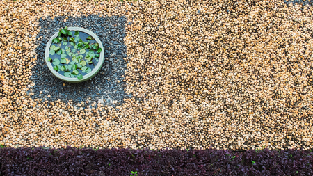 Top View of Vintage Garden with Colorful Pebble Stones on The Ground and Lotus Tub at The Corner with Copyspace used as Template to mock up or input Text Imagens