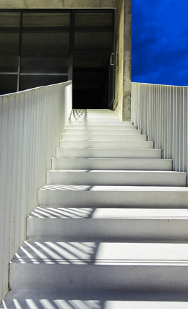 Go Up to The Mystery Concept. Abstract White Granite Stairs with Shadow from the Handrails for Walking Up To The Dark Room with Concrete Wall Imagens