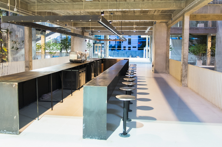 Empty Modern Style of Open Kitchen with Long Counter Bar in Metallic Concept with Many Chairs in The Open-Air Building for Interior Foto de archivo
