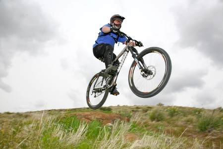 A downhill moutainbiker jumping over a natural ramp  photo