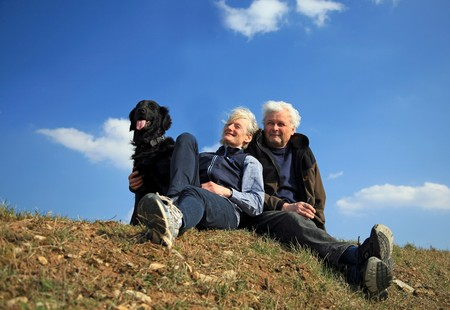 An elderly married couple taking their dog for a walk  photo