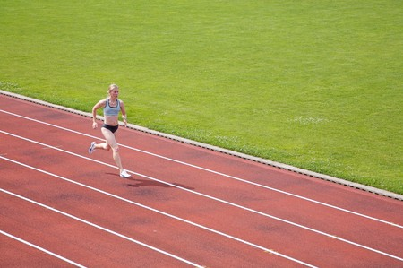 A female athlete running on a track in summer Stock Photo - 4486950