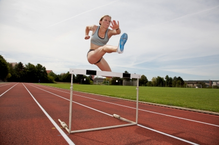obstacle course: A young athlete jumping over a hurdle Stock Photo