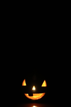 Jack-o-lantern on black background with space for text  Imagens