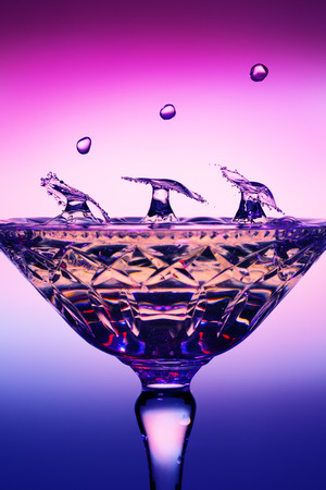 Six water drops collide to form three umbrella shapes in a champagne glass Banco de Imagens