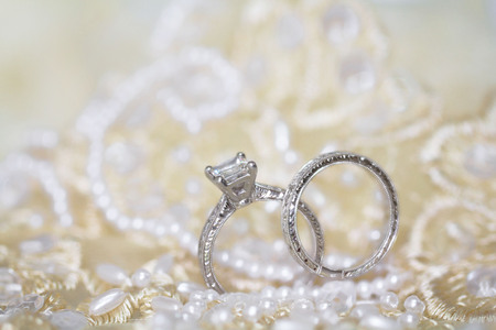 A brides diamond wedding and engagement rings set in white gold and sitting on pearl embroidered lace