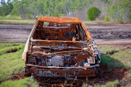 Rusted burnt out car wreck left on mud flats amongst mangroves