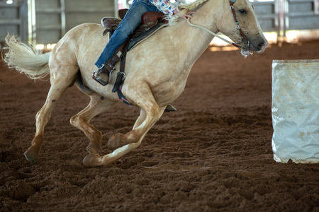 Close up of horse and rider barrel racing at a country rodeo in Australia