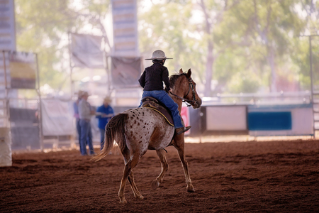 A young rider in jeans and a hard hat competes in a competition at an indoor country rodeo