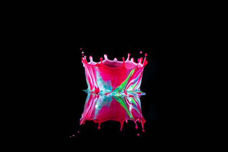 Liquid Drop Art - Water Drop Photography.  Water is dropped into coloured paint placed on a shiny black surface and forms a crown shape, which is reflected on the dark background. Stockfoto