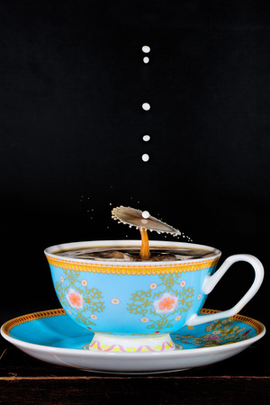 Liquid Drop Art - Water Drop Photography.  Milk is dropped into a cup of coffee and drops collide in the shape of an umbrella, with other milk drops still falling.