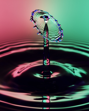 Liquid Drop Art - Water Drop Photography.  An umbrella shape water drop with a red and green coloured background caused by gels on the flashes that froze the action.